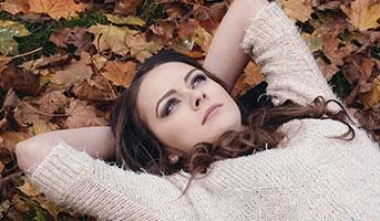 Frau liegt im Herbstlaub