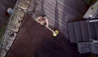 Mann beim Reinigen der Terrasse